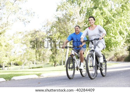 Senior Couple Cycling In Park - stock photo