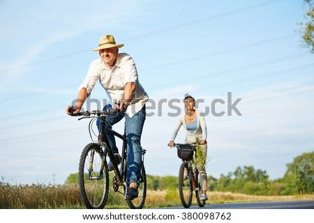 Senior couple cycling with bikes in nature in summer - stock photo
