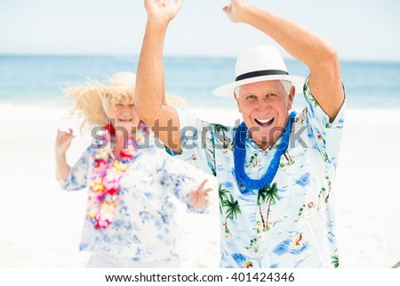 Senior couple dancing at the beach on a sunny day - stock photo