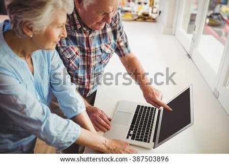 Senior couple discussing while using laptop at home - stock photo