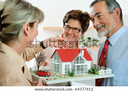 senior couple discussing  with consultant, real estate agent or architect - stock photo