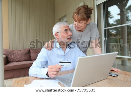 Senior couple doing online shopping - stock photo