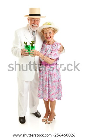 Senior couple dressed up for the Kentucky Derby, drinking mint juleps.  Full body isolated on white.