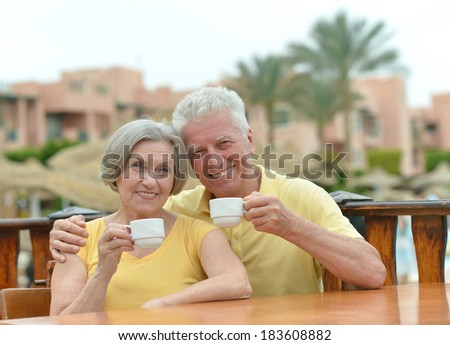 Senior couple drinking coffee outside at the resort during vacation - stock photo