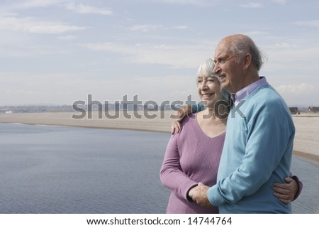 Senior couple embrace by the sea. - stock photo