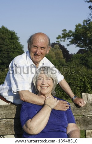 Senior couple embrace in a park. - stock photo