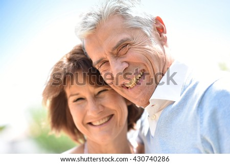 Senior couple embracing each other outside