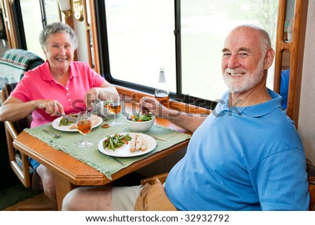Senior couple enjoying a romantic dinner in their motor home.  Focus on husband in foreground. - stock photo