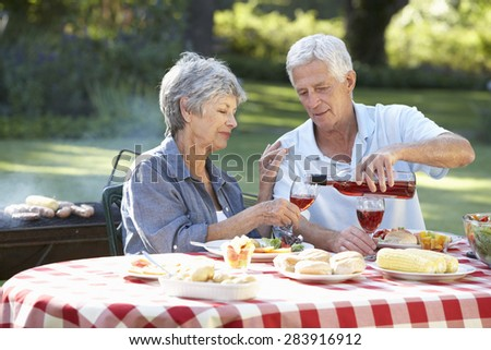 Senior Couple Enjoying Barbeque In Garden Together