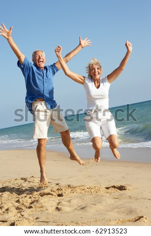 Senior Couple Enjoying Beach Holiday Jumping In Air - stock photo