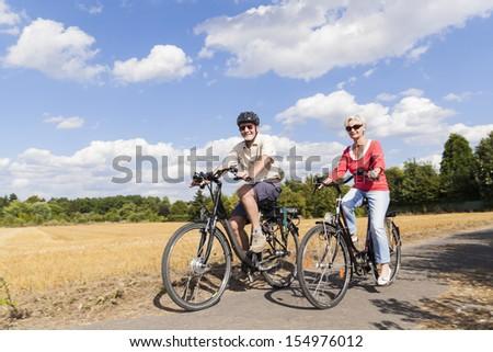 senior couple enjoying bike trip - stock photo