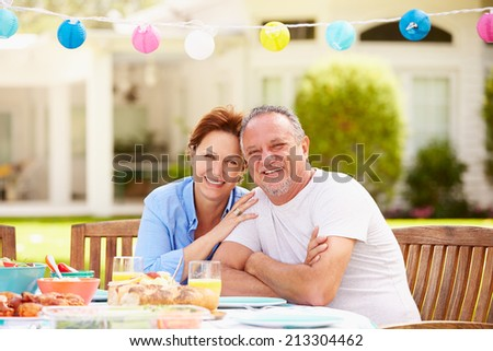 Senior Couple Enjoying Meal In Garden Together - stock photo