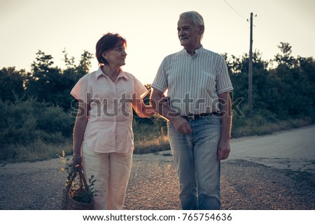 Senior couple enjoying summer sunset in nature