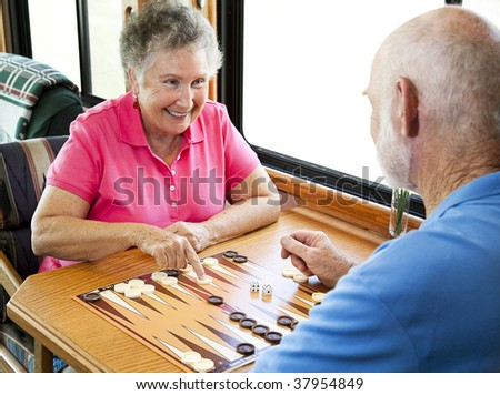 Senior couple enjoys a game of backgammon in their motor home. - stock photo