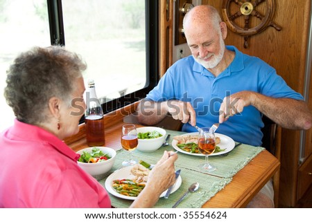 Senior couple enjoys a healthy meal in the kitchen of their RV. - stock photo
