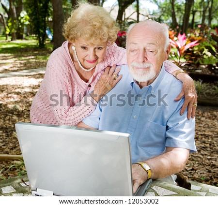 Senior couple enjoys using their computer outdoors. - stock photo