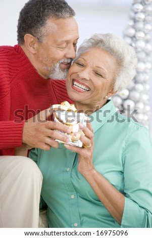 Senior Couple Exchanging A Christmas Gift - stock photo