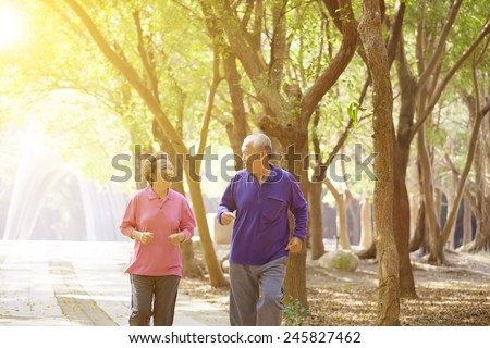 Senior Couple Exercising In Park - stock photo