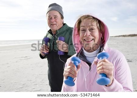 Senior couple exercising on beach lifting hand weights - stock photo