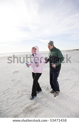 Senior couple exercising, walking on beach with hand weights - stock photo