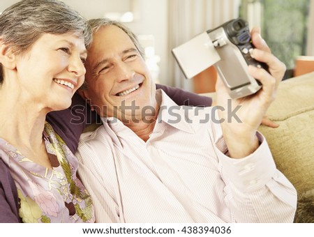 Senior couple filming themselves at home