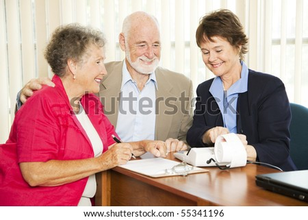 Senior couple gets good financial news from their accountant. - stock photo