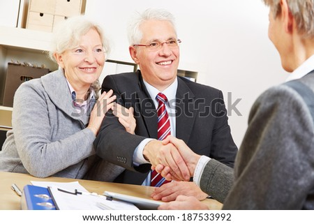 Senior couple giving handshake to consultant for a greeting - stock photo