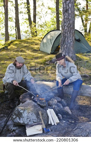Senior couple grill sausages over camp fire using sticks