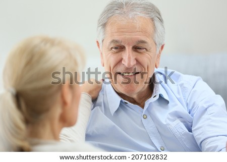 Senior couple having a conversation, sitting in sofa