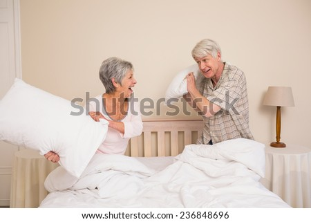 Senior couple having a pillow fight at home in the bedroom - stock photo