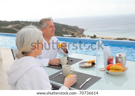 Senior couple having breakfast outside - stock photo