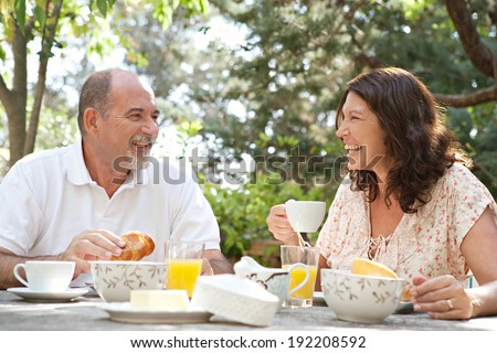 Senior couple having breakfast together at a table in a luxury hotel garden during a sunny day. Mature joyful people eating healthy food and having fun while drinking coffee. Outdoors lifestyle. - stock photo