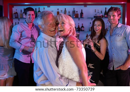 Senior Couple Having Fun In Busy Bar - stock photo