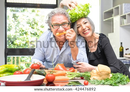 Senior couple having fun in kitchen with healthy food - Retired people cooking meal at home with man and woman preparing lunch with bio vegetables - Happy elderly concept with mature funny pensioner  - stock photo