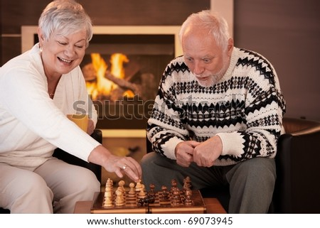 Senior couple having fun with chess at home on winter night woman moving chess man on board, man looking surprised. - stock photo