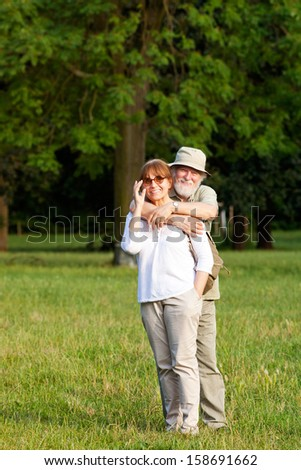 Senior couple having good time outdoors, shallow depth of field - stock photo