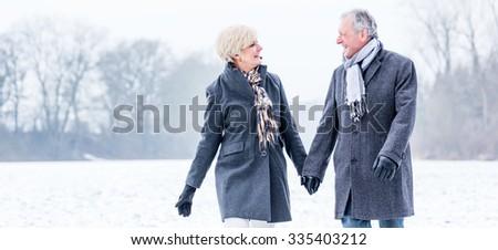 Senior couple having walk in winter - stock photo