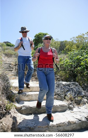 Senior couple hiking at the seafront - stock photo