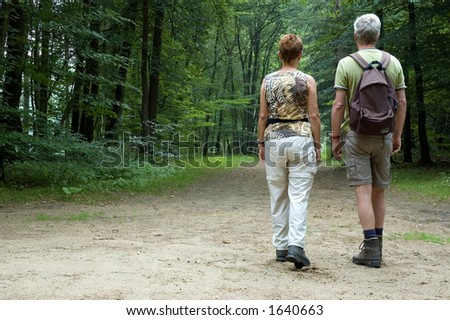 Senior couple hiking in the woods - stock photo