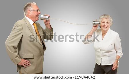 Senior Couple Holding A Tin On Gray Background - stock photo