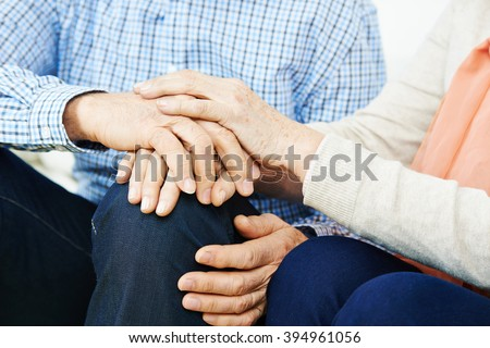 Senior couple holding hands at home for comfort - stock photo