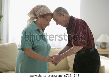 Senior couple holding hands in living room - stock photo