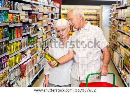 Senior couple holding oil bottle at the supermarket