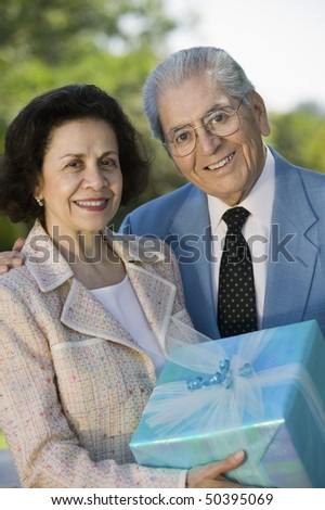 Senior couple Holding present outside, portrait - stock photo