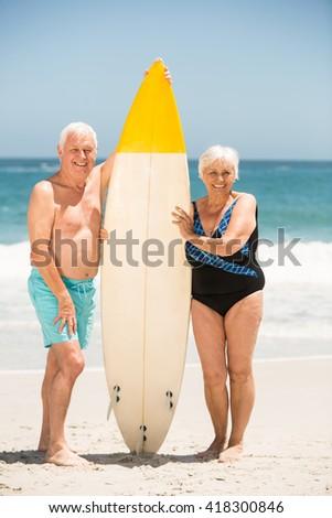 Senior couple holding surfboard on a sunny day - stock photo