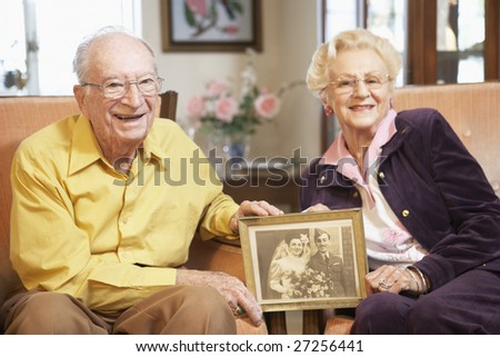 Senior couple holding wedding photo - stock photo