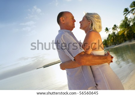 Senior couple hugging at the beach - stock photo