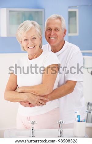 Senior couple hugging in bathroom - stock photo