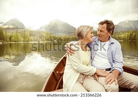 Senior couple hugging on boat on mountain tarn - stock photo