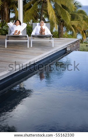 Senior couple in bathrobe lying on deck chairs next to a swimming pool - stock photo
